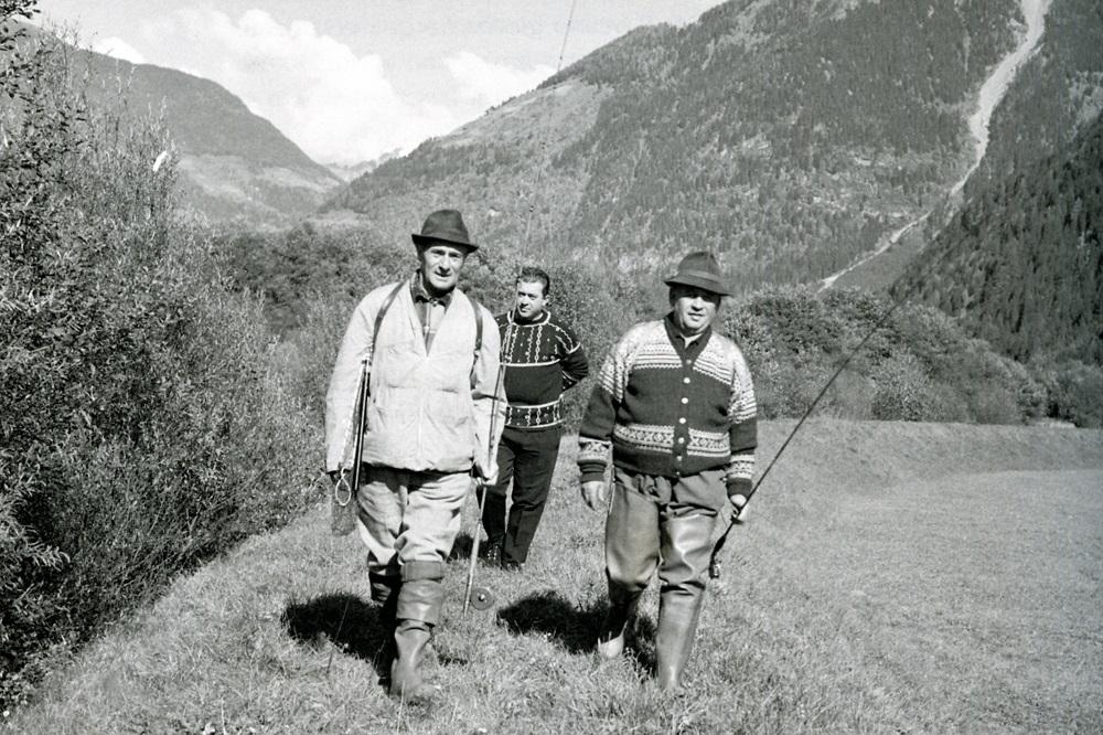 (Archivio storico Eni) Estate '62. Enrico Mattei, Peter Hitthaler a pesca lungo il fiume Aurino con la loro guardia del corpo Ottavio Rapetti